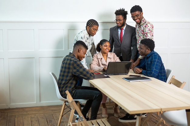 Team van jonge afrikaanse mensen werkzaam in kantoor aan tafel met laptop
