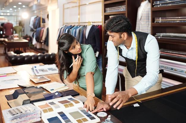 Team van jonge indiase kleermakers die stof uit de catalogus bespreken bij het maken van een nieuwe modecollectie met kledingstukken voor de klant
