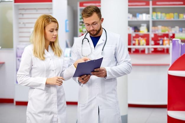 Team van jonge kaukasische chemici of drogisten die geneesmiddelen bespreken