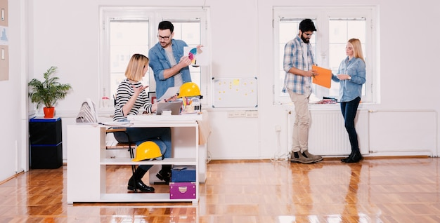Team van jonge moderne hardwerkende ontwerpers die samenwerken in het grote, lichte kantoor.