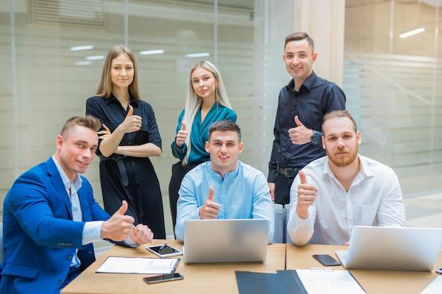 Team van jonge professionals mannen en vrouwen aan het werk op kantoor met een gebaar van handen