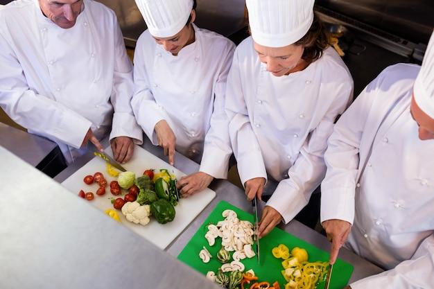 Team van koks die groenten hakken