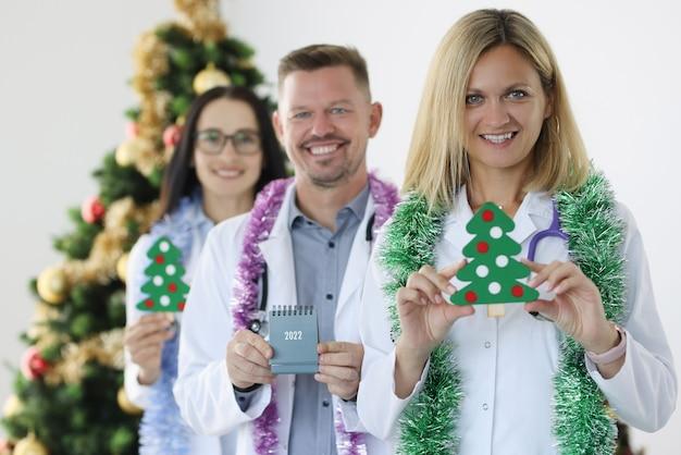 Team van lachende artsen houden kalender voor en kerstboom nieuwjaar en kerst