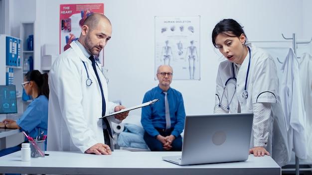 Team van mannelijke en vrouwelijke artsen die het probleem van de oudere patiënt bespreken terwijl hij zich zorgen maakt in het ziekenhuisbed. gezondheidszorg in een modern ziekenhuis of privékliniek, ziektepreventie en consultatie in medic off