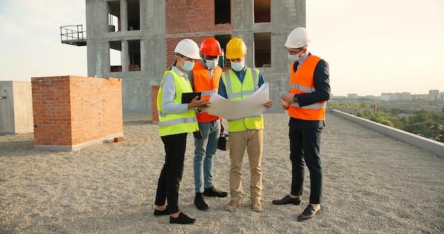 Team van mannelijke en vrouwelijke constructeurs van gemengde rassen in helmen en medische maskers die aan de bovenkant van het gebouw staan en het ontwerp van het bouwplan bespreken. pandemisch concept. ingenieurs en architecten.
