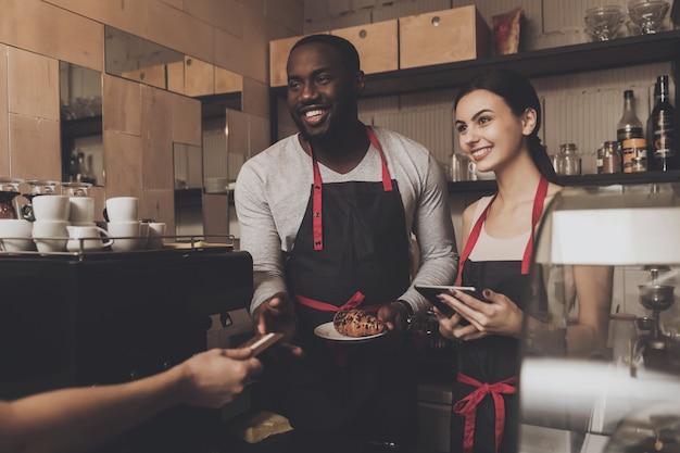 Team van mannelijke en vrouwelijke klanten van de barista-service