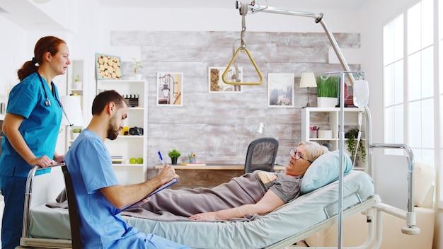 Team van mannelijke en vrouwelijke verpleegsters die een oude dame controleren die in een ziekenhuisbed in een bejaardentehuis ligt