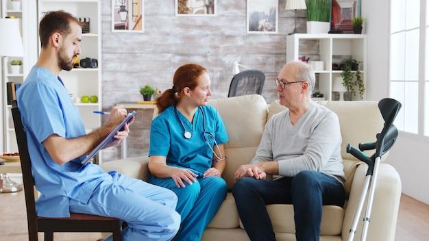 Team van mannelijke en vrouwelijke verpleegsters in gesprek met een oude en gepensioneerde man in een licht en gezellig verpleeghuis