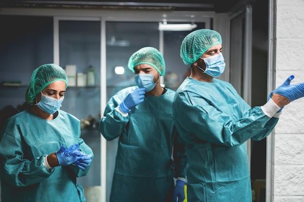 Team van medisch chirurg aan het werk na operatie in het ziekenhuis tijdens uitbraak van coronavirus-pandemie