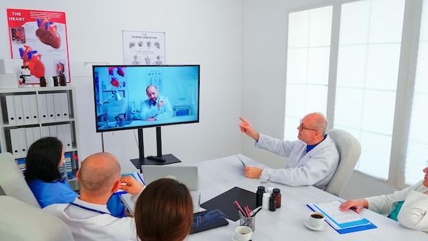 Team van medisch personeel bespreken tijdens videoconferentie met arts in ziekenhuiskantoor. artsen houden online vergadering in bestuurskamer met man-specialist, verpleegster die aantekeningen maakt op klembord.