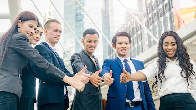 Team van mensen uit het bedrijfsleven duimen opdagen