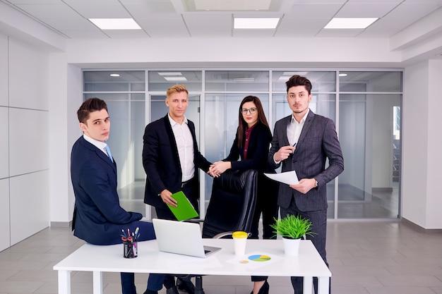 Team van mensen uit het bedrijfsleven werken aan een bureau in een modern kantoor