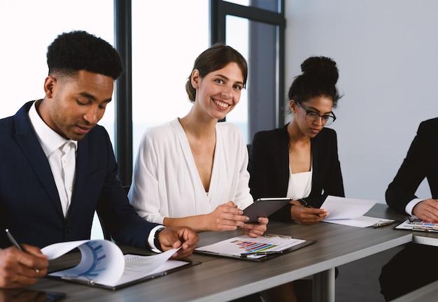 Team van mensen werken samen op kantoor met bedrijfsstatistieken. concept van teamwerk en partnerschap.