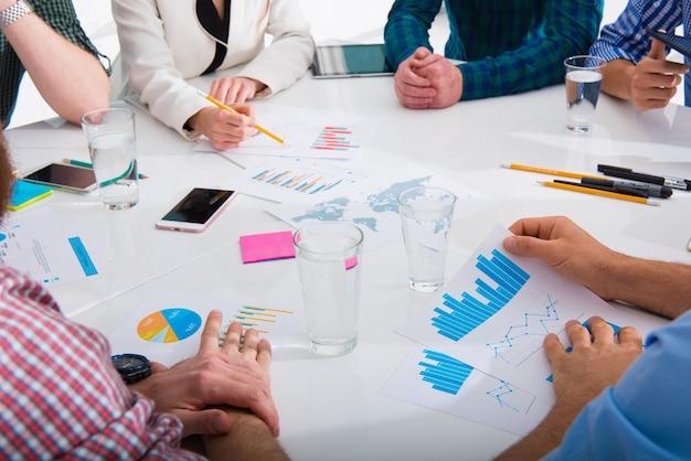 Team van mensen werkt samen aan bedrijfsstatistieken op kantoor. concept van teamwerk en partnerschap