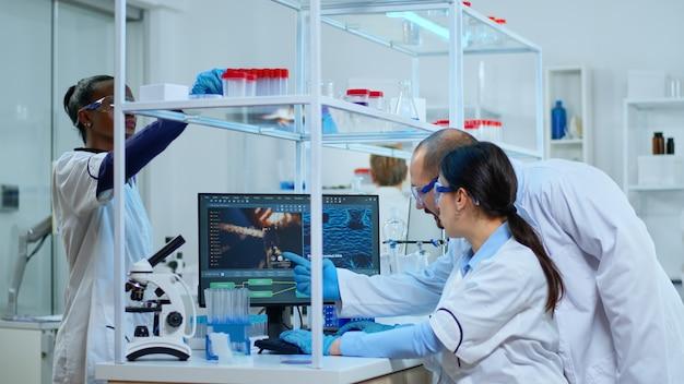 Team van microbiologische wetenschappers die discussiëren over de ontwikkeling van virussen in een modern uitgerust laboratorium met behulp van computer die testbloedmonsters analyseert en vaccin, medicijnen en antibiotica tegen covid-19 ontwikkelt.