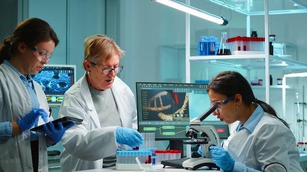Team van microbiologische wetenschappers die discussiëren over virusontwikkeling die overuren maakt in een modern uitgerust laboratorium dat testbloedmonsters analyseert en vaccin, medicijnen en antibiotica ontwikkelt tegen covid-19.