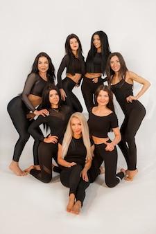 Team van mooie jonge vrouwen in zwarte trainingspakken op een witte achtergrond