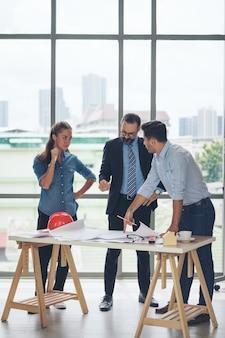 Team van multi-etnische architecten bezig met bouwplannen in de vergaderruimte. ingenieurs bespreken op project in kantoor. rijpe zakenman en vrouw die zich rond lijst bevinden die aan blauwdruk werken.