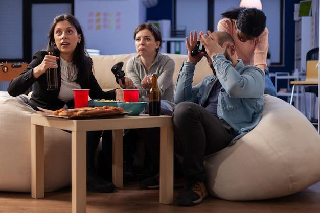 Team van multi-etnische vrienden die tv-game op console verliezen