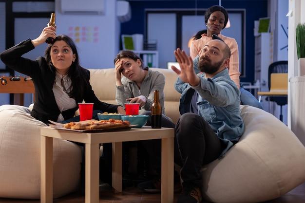 Team van multi-etnische vrienden die tv-spel op console verliezen na het werk op kantoor