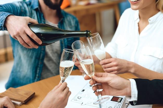 Team van ontwerpersarchitecten die champagne gieten.