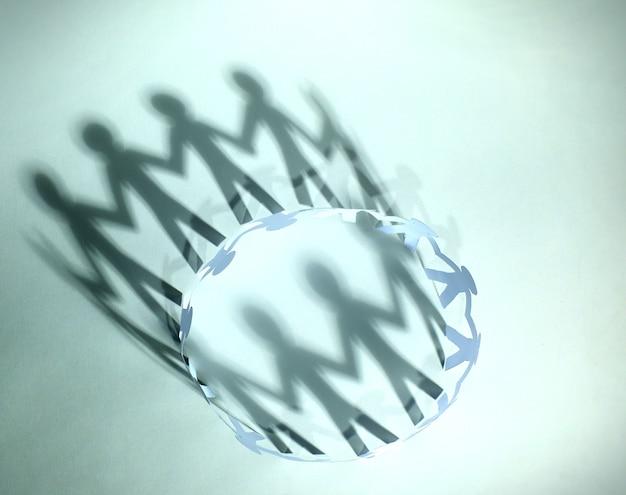 Team van papieren poppetjes die elkaars hand vasthouden