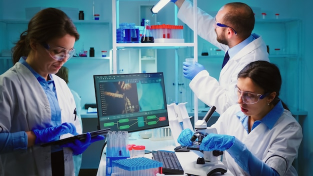Team van positieve wetenschappers die werken in een met chemie uitgerust laboratorium, verpleegster die op tablet typt