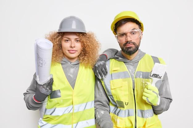 Team van professionele architecten gekleed in uniform werk samen houden blauwdruk en verfborstelwerk voor bouwconstructieproject ter plaatse