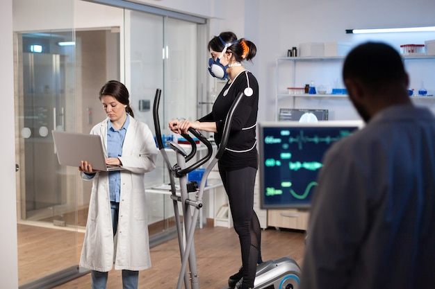 Team van professionele artsen die de gezondheidstoestand van vrouwelijke atleet meten in het wetenschapssportlaboratorium. arts die laptop gebruikt om ecg-gegevens, spieruithoudingsvermogen, psychologische weerstand van de hartslag te controleren