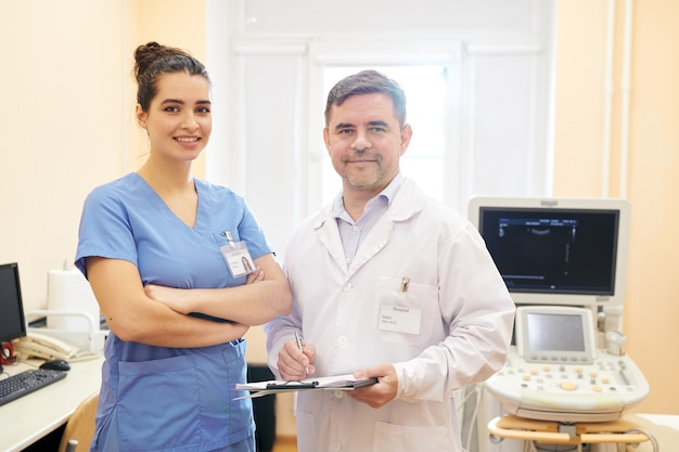 Team van professionele artsen met badges op kisten staan in echografie procedure kamer en camera kijken