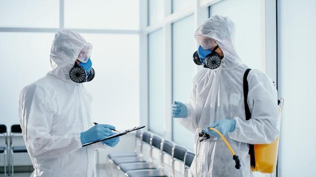 Team van professionele desinfector die een verslag maakt van het verrichte werk