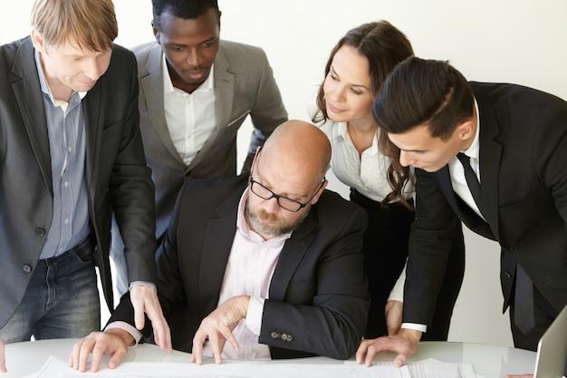 Team van professionele ingenieurs die werken aan bouwproject in de directiekamer, blauwdrukken analyseren, er serieus en geconcentreerd uitzien.