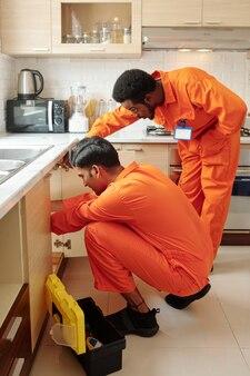 Team van professionele loodgieters die pijp onder gootsteen in keuken bevestigen en lek herstellen