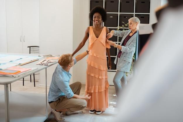 Team van professionele ontwerpers die voor een lachend model in een nieuwe jurk staan