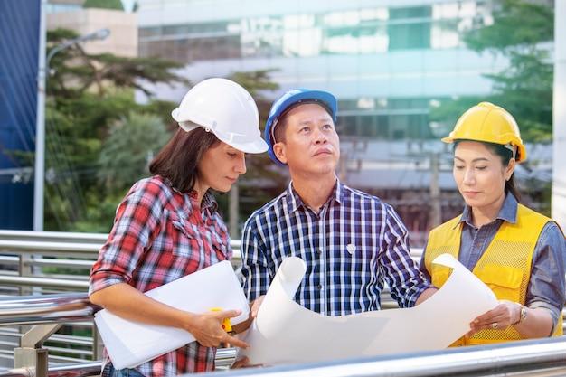 Team van projectingenieur architect en kwaliteitscontrole werken samen op de bouwplaats.