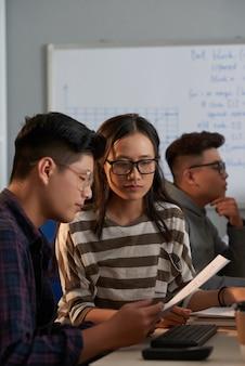 Team van serieuze jonge softwaretesters die bugrapport bespreken aan kantoortafel