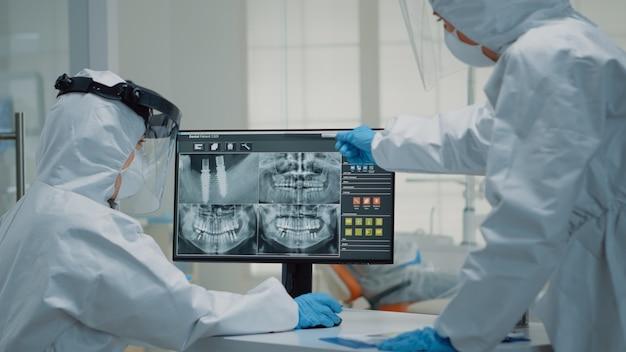 Team van stomatologen die tandheelkundige röntgenscan analyseren