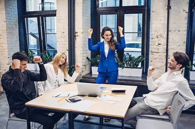 Team van succesvolle ondernemers vieren aan tafel op kantoor