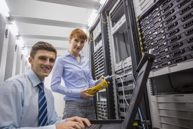 Team van technici die digitale kabelanalysator op servers gebruiken