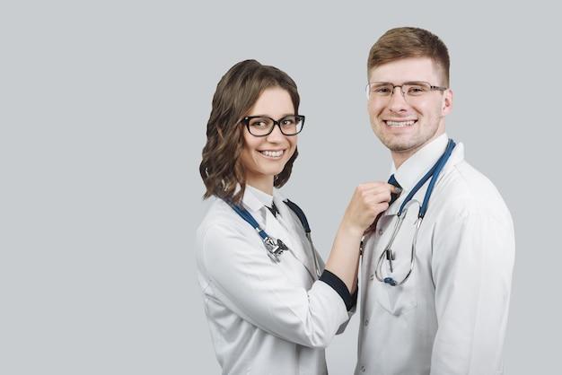 Team van twee artsen man en vrouw staan nauw lachend terwijl kijken naar camera geïsoleerd op een grijze achtergrond met kopie ruimte