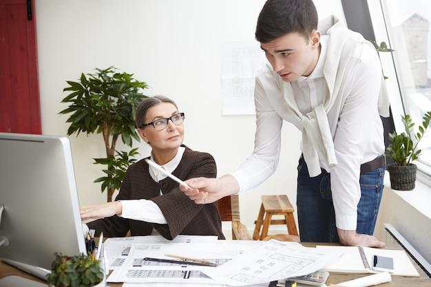 Team van twee bekwame architecten jonge man en oudere vrouw ontwikkeling van nieuw woonhuisvestingsproject, werken op generieke computer in kantoor, met behulp van cad-programma, man wijzend op scherm met potlood