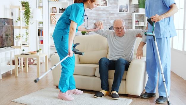Team van verpleegsters of maatschappelijk werkers die een oude gehandicapte man helpen om met zijn krukken de verpleegkamer uit te lopen.