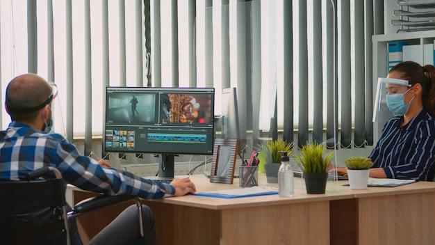 Team van videografen met beschermingsmaskers die werken bij een videoproject dat inhoud creëert, man-blogger die in een rolstoel zit in een nieuw normaal kantoor. uitgeschakelde freelancer die video bewerkt tijdens wereldwijde pandemie