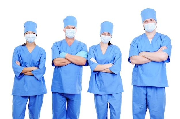 Team van vier chirurgen in blauw uniform die zich verenigen