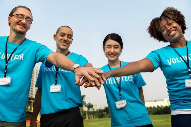 Team van vrijwilligers die handen stapelen