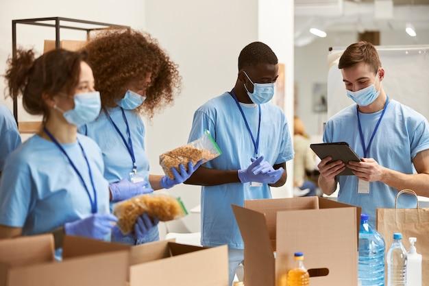 Team van vrijwilligers met beschermende maskers en handschoenen die voedsel sorteren in kartonnen dozen aan het werk