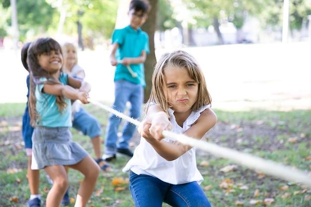 Team van vrolijke kinderen die touw trekken, touwtrekken spelen, genieten van buitenactiviteiten. groep kinderen plezier in park. jeugd of teamwerk concept
