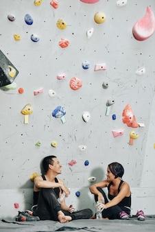 Team van vrolijke klimmers op blote voeten die aan de bouldermuur zitten, water drinken en praten na de training