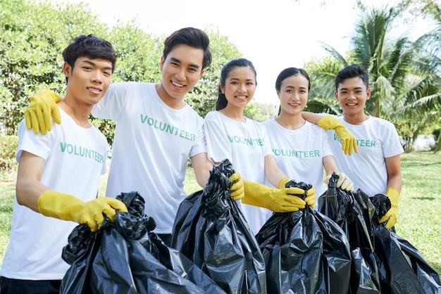 Team van vrolijke vrijwilligers in handschoenen die vuilniszakken vasthouden en naar de camera glimlachen na het verzamelen van afval in het plaatselijke park