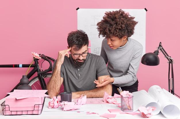 Team van vrouwelijke en mannelijke studenten werken samen aan schets van bouwplanning, werken samen aan het oplossen van problemen op de desktop hebben verbaasde uitdrukkingen
